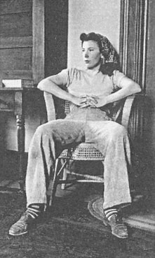 Isabel Bloom sitting in a chair with hands folded and fingers intertwined