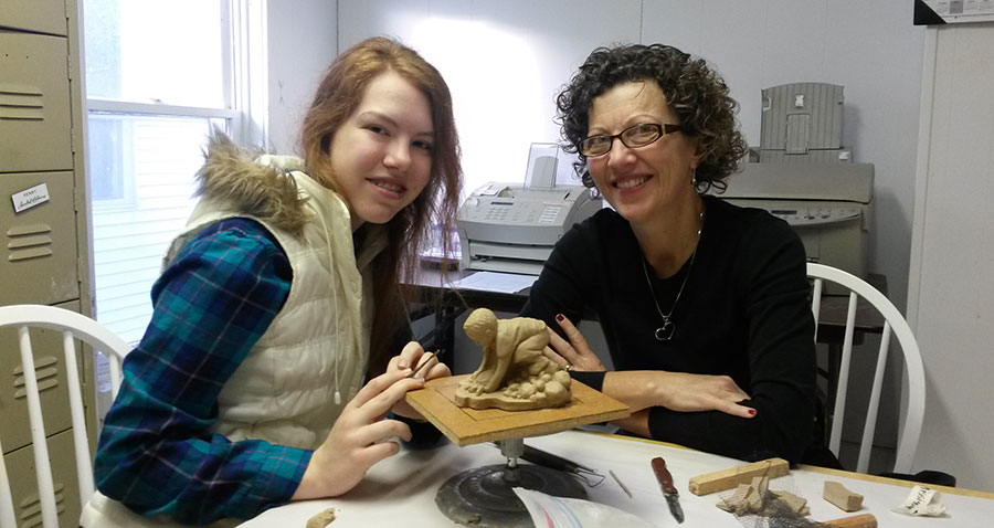 Donna pictured with teen with new clay model for an upcoming sculpture.
