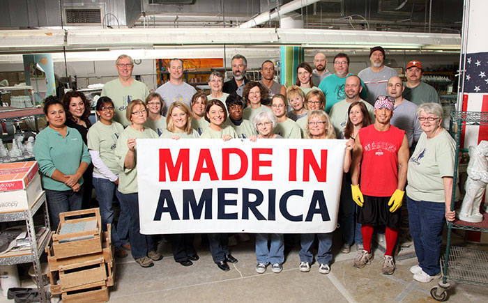 Isabel Bloom staff holding a large 'Made in America' sign in their workshop.