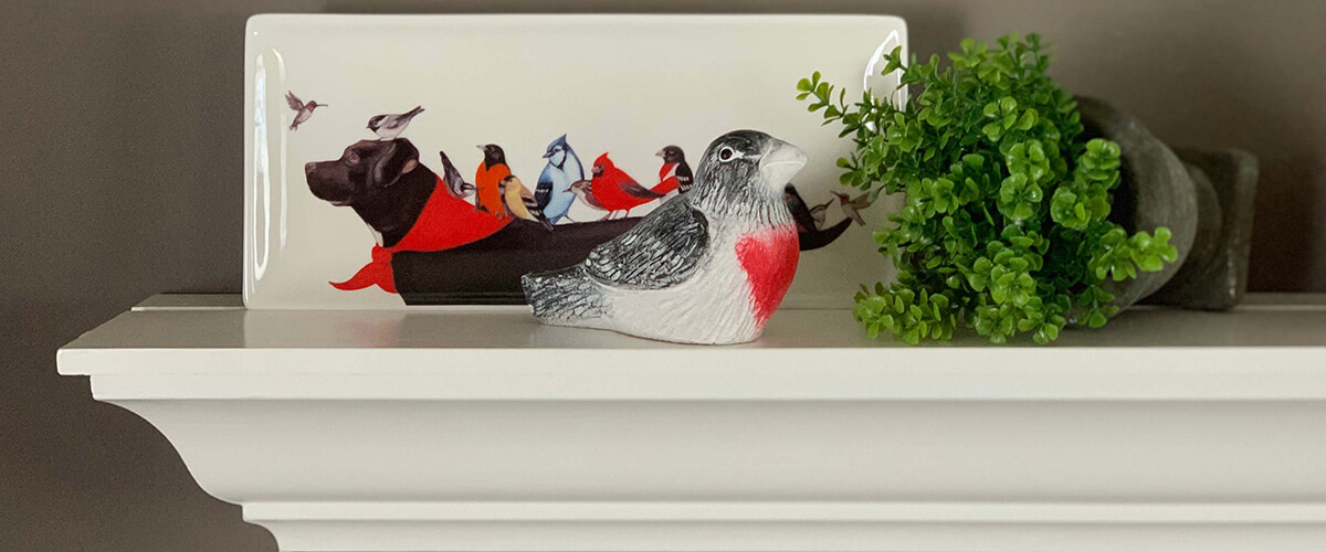 Rose Breasted Bird sculpture shown on a mantle